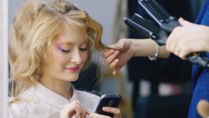 Девушка отправляет СМС в салоне красоты